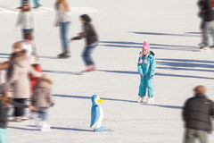 Little girl in winter clothes skating on ice rink Stock Images