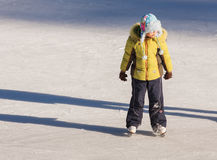 Little girl in winter clothes skating on ice rink Royalty Free Stock Photo