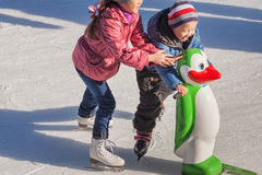 Little girl in winter clothes skating on ice rink Royalty Free Stock Images