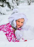 Little girl in winter clothes under snow fir tree. Stock Photos