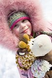 Little girl in winter clothing. Smiling little girl in winter clothing holding toy in her hands Royalty Free Stock Images