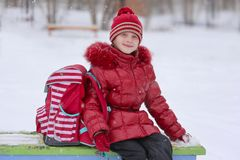 Cute little girl with a portfolio after school. Little girl on a winter day with a school backpack Stock Images