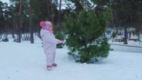 Little girl in the winter forest plays and smiles stock footage