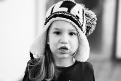 Little girl with winter hat making funny faces Royalty Free Stock Photo