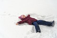 Little girl in winter outdoors. Little cute girl in winter outdoors. She makes snow angel. Girl rejoices and fools stock photo
