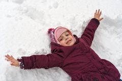 Little girl in winter outdoors. Little cute girl in winter outdoors. She makes snow angel. Girl rejoices and fools. Close-ups royalty free stock photos