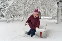 Little girl in winter outdoors. Little cute girl in winter outdoors. She shakes off snow from bench. Girl rejoices and fools stock image