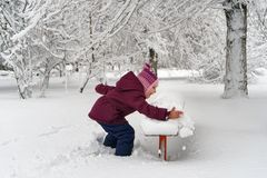 Little girl in winter outdoors. Little cute girl in winter outdoors. She shakes snow off bench. Girl rejoices and fools stock photo