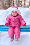 Little girl in winter outerwear sit on  bench. Royalty Free Stock Photos