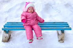 Little girl in winter outerwear sit on  bench. Stock Image