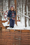 Little girl in winter park. A caucasian 4 years old girl on wooden toy-ship Stock Image