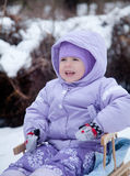 Little girl in a winter park on a sled Stock Photo