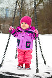 Little girl on winter seesaw Stock Photos
