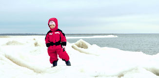 Little girl on winter snow-covered coast Stock Photos