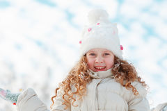 little girl on a winter walk on clouds sky background. Stock Photos