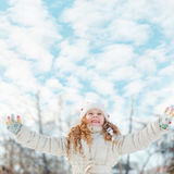 Little girl on a winter walk on clouds sky background. Royalty Free Stock Image