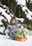 Little girl in a winter wood with the big basket Royalty Free Stock Photos