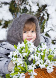 Little girl in a winter wood with the big basket of snowdrops Royalty Free Stock Photo