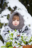 Little girl in a winter wood with the big basket of snowdrops Royalty Free Stock Image