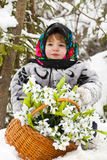 Little girl in a winter wood with the big basket of snowdrops Royalty Free Stock Photos