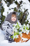 Little girl in a winter wood with the big basket of snowdrops Stock Photos
