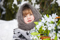 Little girl in a winter wood with the big basket of snowdrops Royalty Free Stock Photography