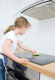 Little girl wipes cooktop. Stock Photography