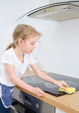 Little girl wipes cooktop. Royalty Free Stock Images