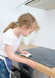Little girl wipes cooktop. Royalty Free Stock Photos