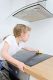 Little girl wipes cooktop. Royalty Free Stock Photo