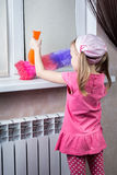 Little girl wipes dust with brush. Little girl wipes dust with a brush Royalty Free Stock Image