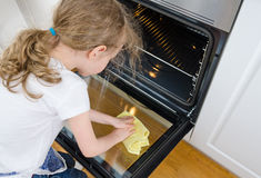 Little girl wipes oven. Royalty Free Stock Photography
