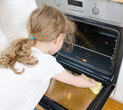Little girl wipes oven. Royalty Free Stock Images
