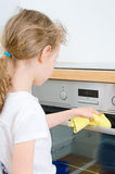 Little girl wipes oven. Royalty Free Stock Image