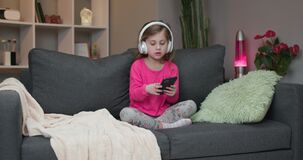 Little girl in wireless headphones dancing and moving to the rythm. Kid in headphones. Happy little girl listening to
