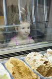 Little girl wishes ice cream in pastry shop. Reflections on ice cream counter glasses Royalty Free Stock Images