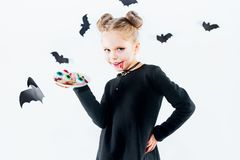 Little girl witch in black dress over magical accessories. Halloween, the studio evening. Little girl witch in black long dress and magical accessories Royalty Free Stock Photo