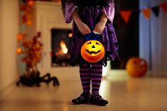 Kids in witch costume on Halloween trick or treat stock images