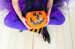 Little girl a witch costume holding a pumpkin. stock photography