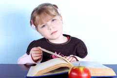 Little Girl With Apple And Books Royalty Free Stock Photos