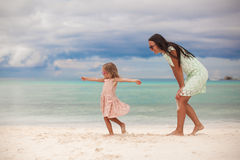 Little Girl With Her Mother Dancing At White Sandy