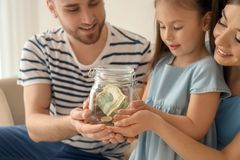 Little Girl With Her Parents Holding Glass Jar With Dollars Indoors. Money Savings Concept Royalty Free Stock Images