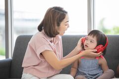 Free Little Girl With Learning Disabilities Or The Group Of Dow Syndrome Is Listening Music From Headphone With Mother Teaching And Royalty Free Stock Photos - 192014738