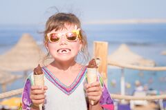Free Little Girl Without Front Teeth, Holds Chocolate Ice Cream Cone In Hand. Cheerful Child With Two Ice Cream On The Beach. Babe In Stock Photography - 176373132