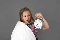 Little girl woke up too late. Little girl wrapped in blanket with alarm clock in hand panics thinking she woke up too late on gray background - Morning time and Royalty Free Stock Images