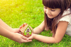 Little girl and a woman hands holding small house on a backgroun Royalty Free Stock Image