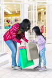 Little girl and woman looking shopping bag Stock Photos