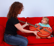 Little girl and woman play with electric guitar Royalty Free Stock Images