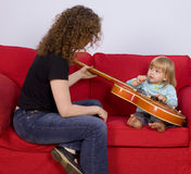 Little girl and woman play with electric guitar Stock Photo