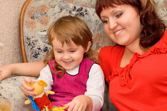Little girl and woman play toy in cosy room Royalty Free Stock Images